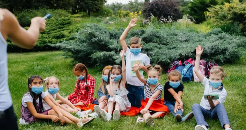 A group of children wearing masks and sitting in a garden