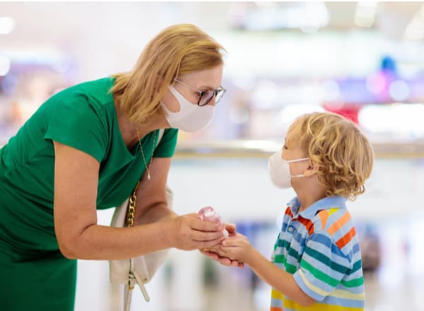 A woman and child wearing masks and using hand sanitizer