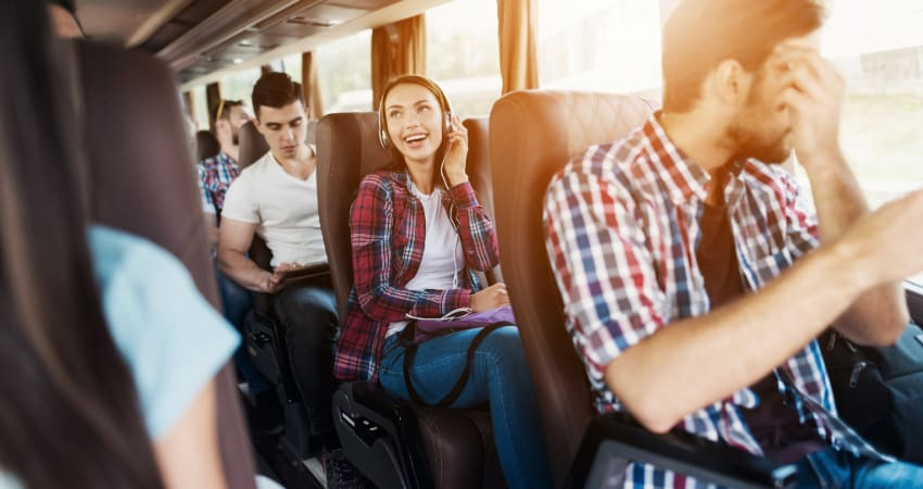 A large group of people sit in a charter bus rental, using their phones or listening to music on headphones