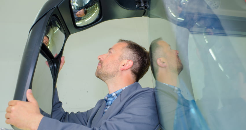 A charter bus driver inspects a bus mirror before a trip