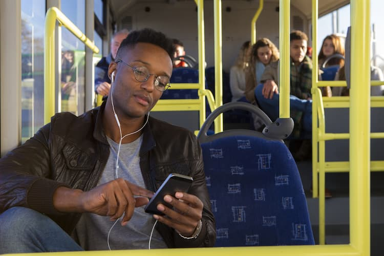 Man listening to music with earphones on bus