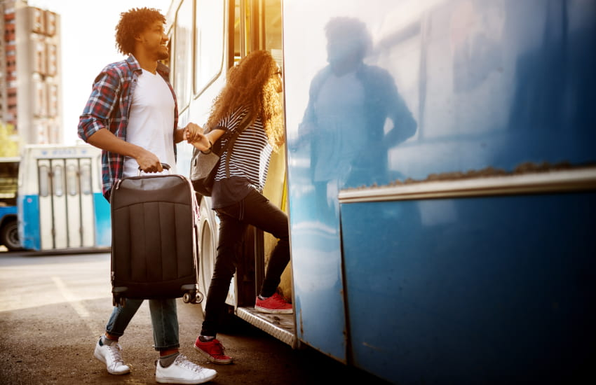 A young couple carries suitcases as they enter a bus