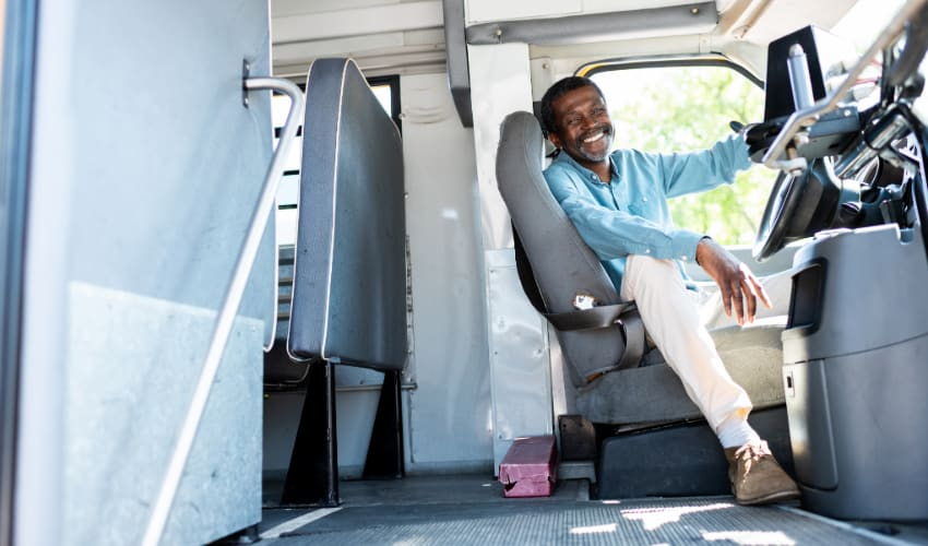 A bus driver smiles and sits in the driver seat of a charter bus