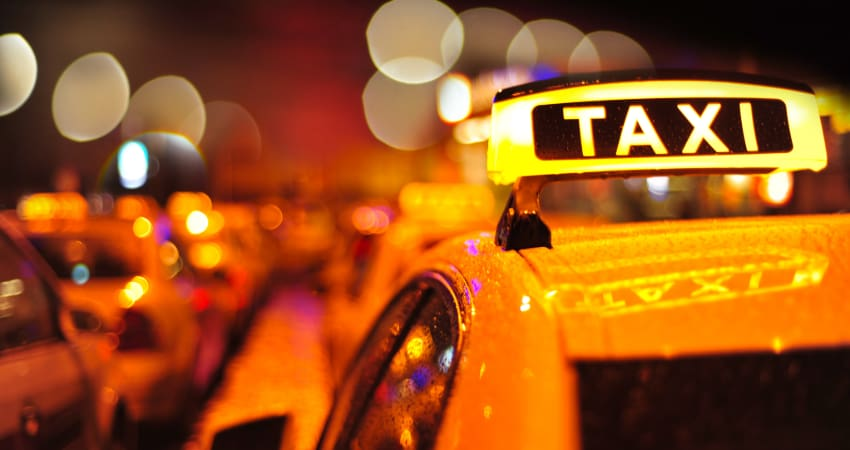 A line of yellow taxicabs sit in city traffic at night