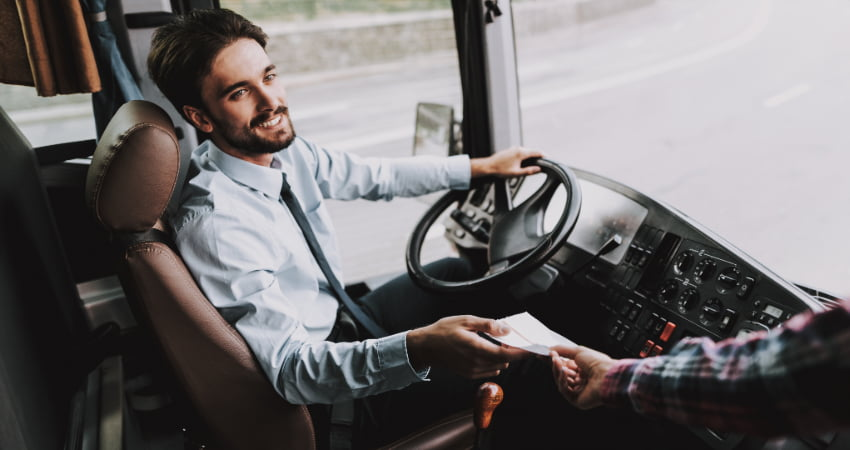 A charter bus driver sits in the driver seat of a bus as a passenger hands them an envelope of money