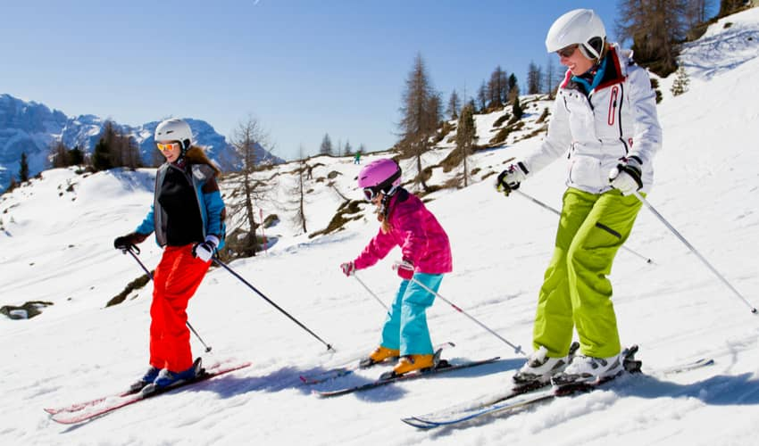 Two adults and a child skiing down a mountain