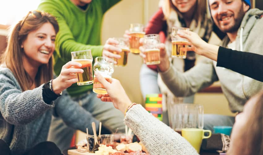 A group of friends toasting drinks after skiing