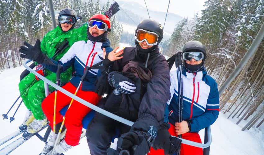 A group of people smiling for selfie on a ski lift