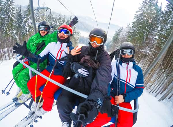 A group of people smiling for a selfie on a ski lift