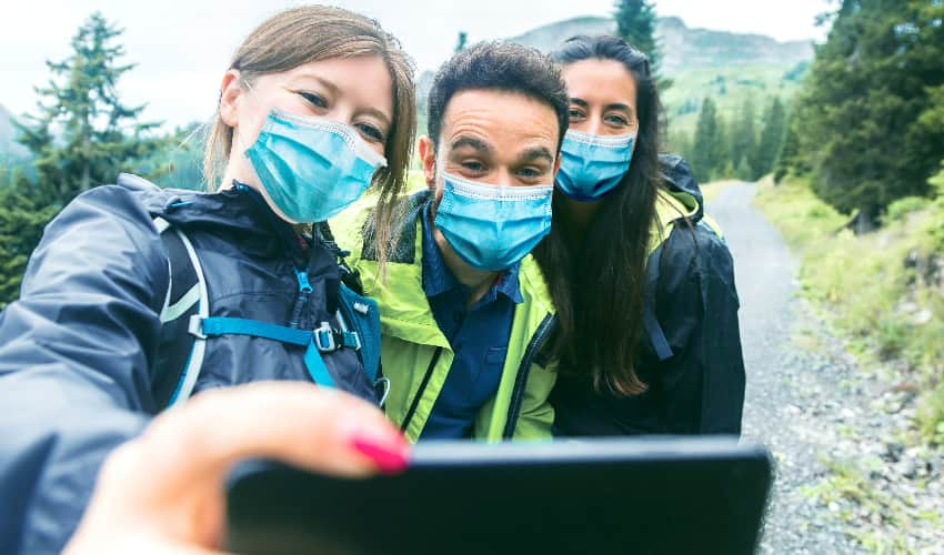 Three hikers in masks take a selfie while on the trail, snowy mountains and green trees in the background