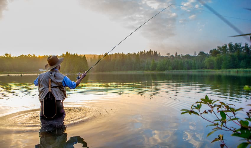 A fly fisherman casts his reel on a peaceful lake at sunrise