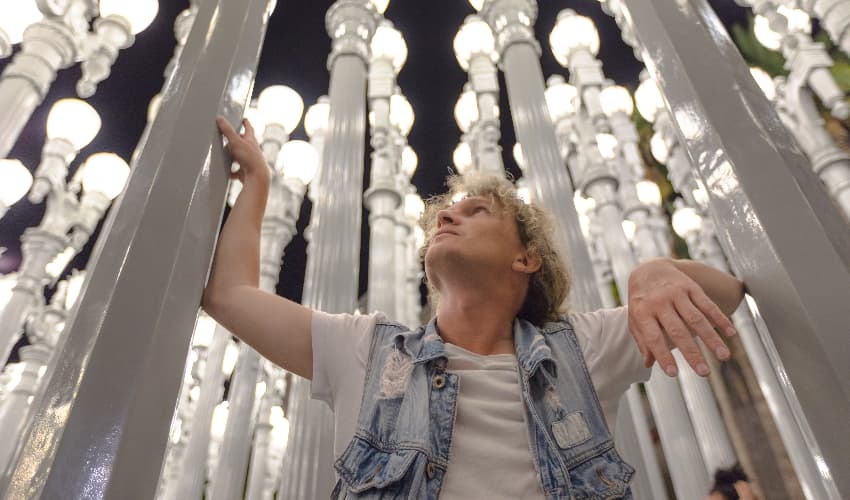 A man poses amidst the Urban Light installation at LACMA