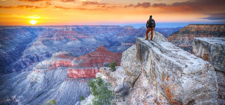 a man stands at a rock summit overlooking the vast and colorful grand canyon