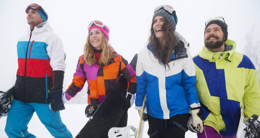 A group of 4 young people in skiing and snowboarding gear