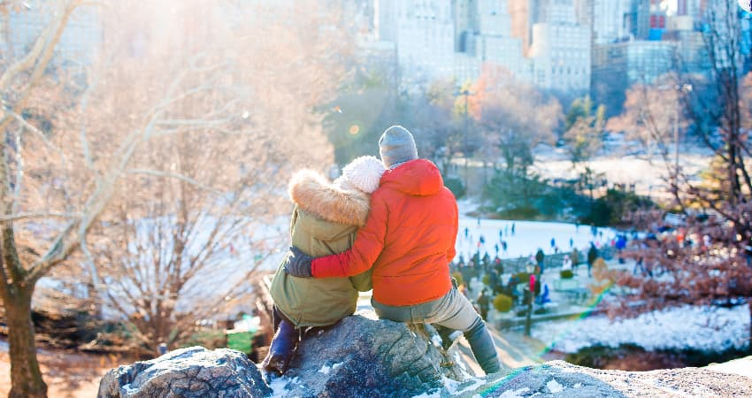 A happy couple in parkas sit on a rock outcropping in Central Park and watch ice skaters below