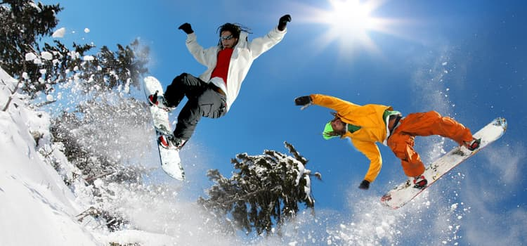 two friends jump over a slope on snowboards while snow flies into the air