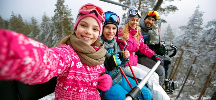 a family on a ski lift smiles for a selfie in the air