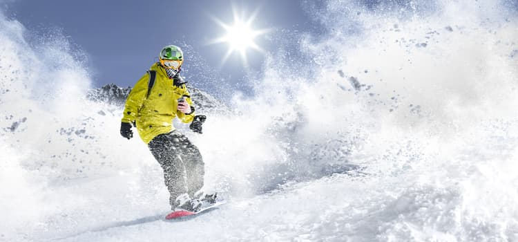 a skier slides down a snowy slope while snow puffs into the air around them