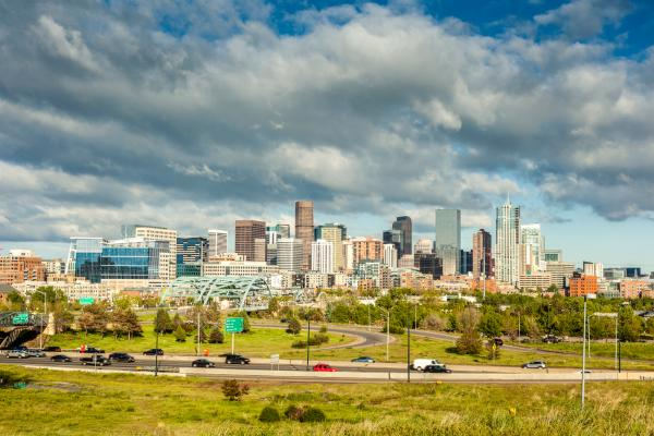 A view of the Denver skyline with a highway and green space in the foreground
