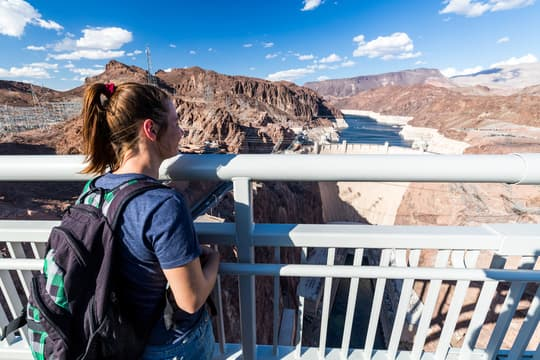 a young student looks at the hoover dam from a high observation point