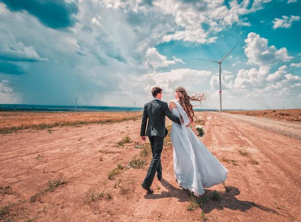 a couple face away from the camera on their wedding day, with the desert in the background