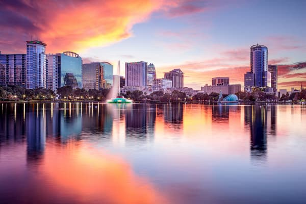 the orlando skyline at sunset over lake eola