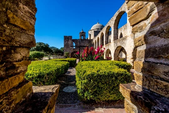 A courtyard filled with plants at a San Antonio Mission