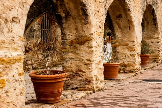 A bride walking through a stone courtyard with arched doorways in the San Antonio Mission