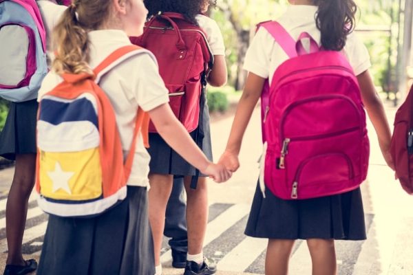 A group of school children holding hands while wearing backpacks