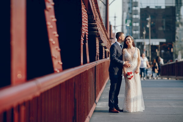 A bride and groom holding hands on an urban street in Chicago