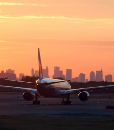 A plane taking off at JFK Airport during sunset with the NYC skyline in the background.