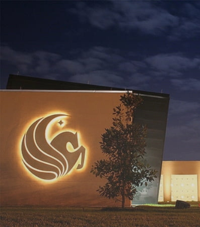The UCF logo illuminated on a campus building at night
