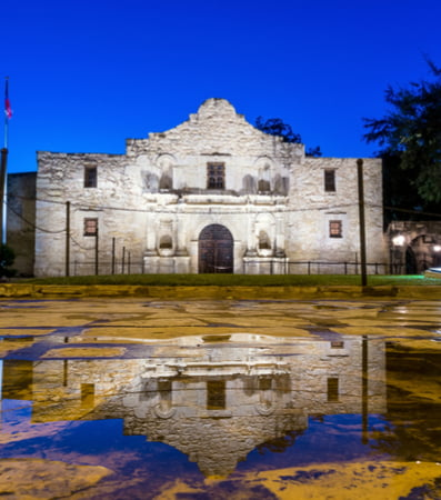 The entrance to The Alamo lit up in the evening.