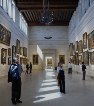 Tourists observing works of art in a gallery