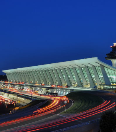 A brightly lit building and glowing pathways at Dulles Airport at night