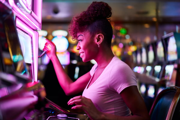 A woman playing a slot machine in a casino.