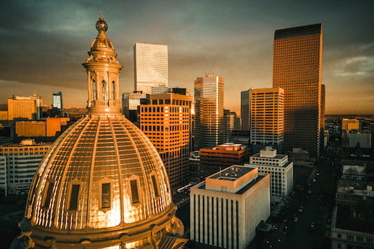 The Denver skyline at sunset, the dome of the State Capitol building at the forefront