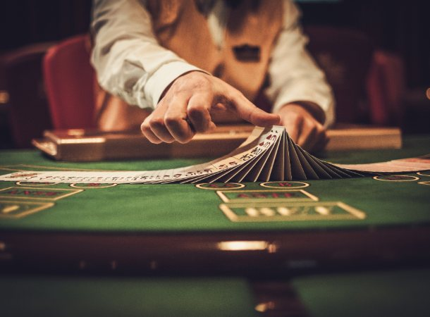 A blackjack dealer shuffles cards in a dimly lit casino