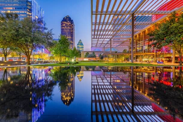 Sun sets over an urban pond in the Dallas Arts District