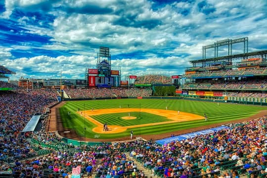 Interior of Coors Field on a game day, fans filling the seats and the sun shining overhead