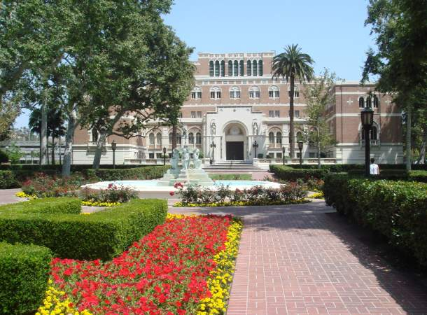 A flower garden and fountain in front of a building on the University of Southern California campus