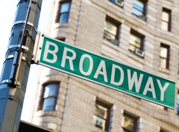 A green street sign in a New York City intersection reads