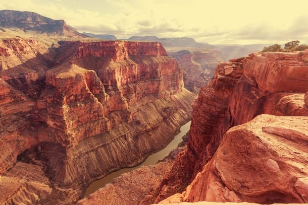 The southern rim of the Grand Canyon at sunset, viewed from the top looking down at the river below