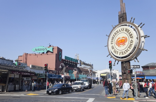 Cars drive by the sign at the entrance of Fisherman's Wharf in San Francisco