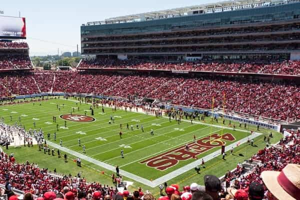 Interior of Levi's Stadium on game day, fans crowding the stands as football players take the field