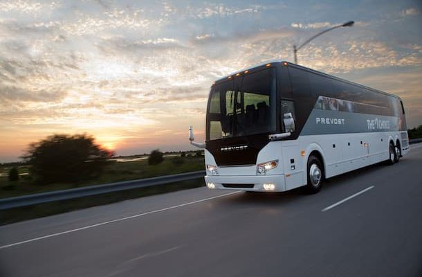 Prevost bus driving down street at sunset