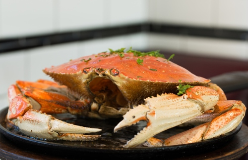 a dinner platter with a whole crab