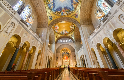 beautiful gold and white interior with stained glass windows of the washington national cathedral