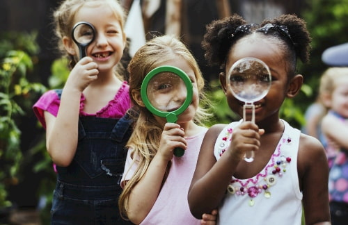 kids look through magnifying glasses