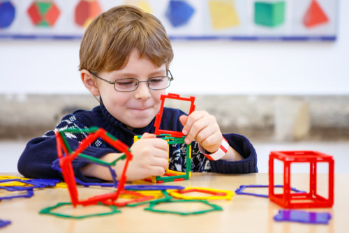 boy plays with building pieces at children's museum